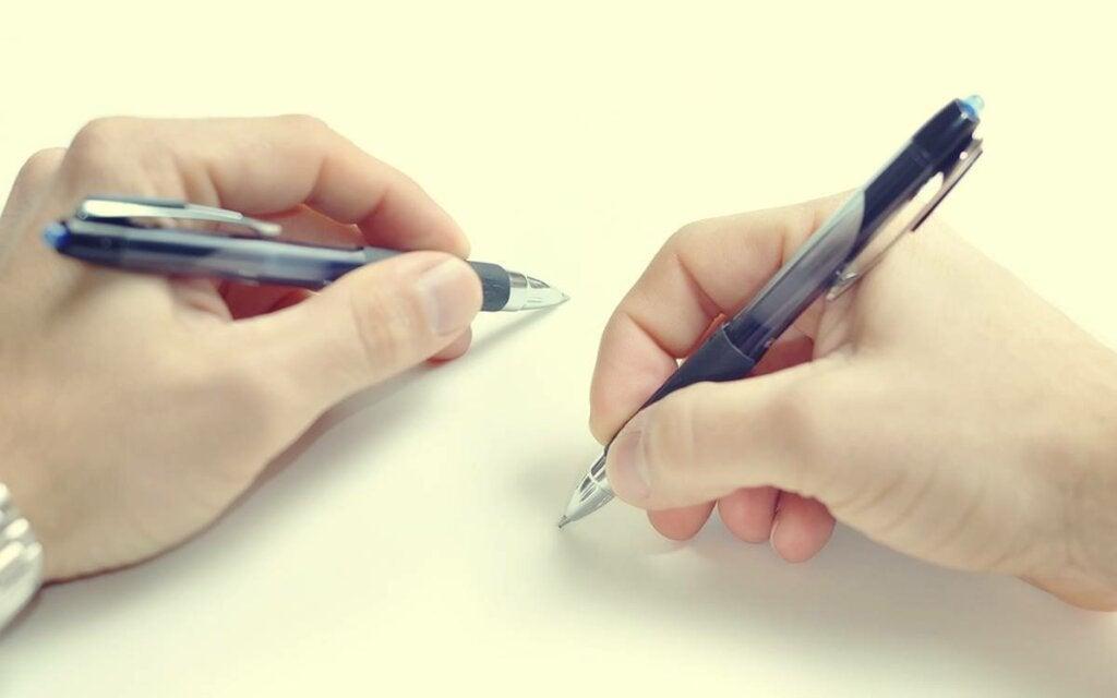 Manos con dos bolígrafos