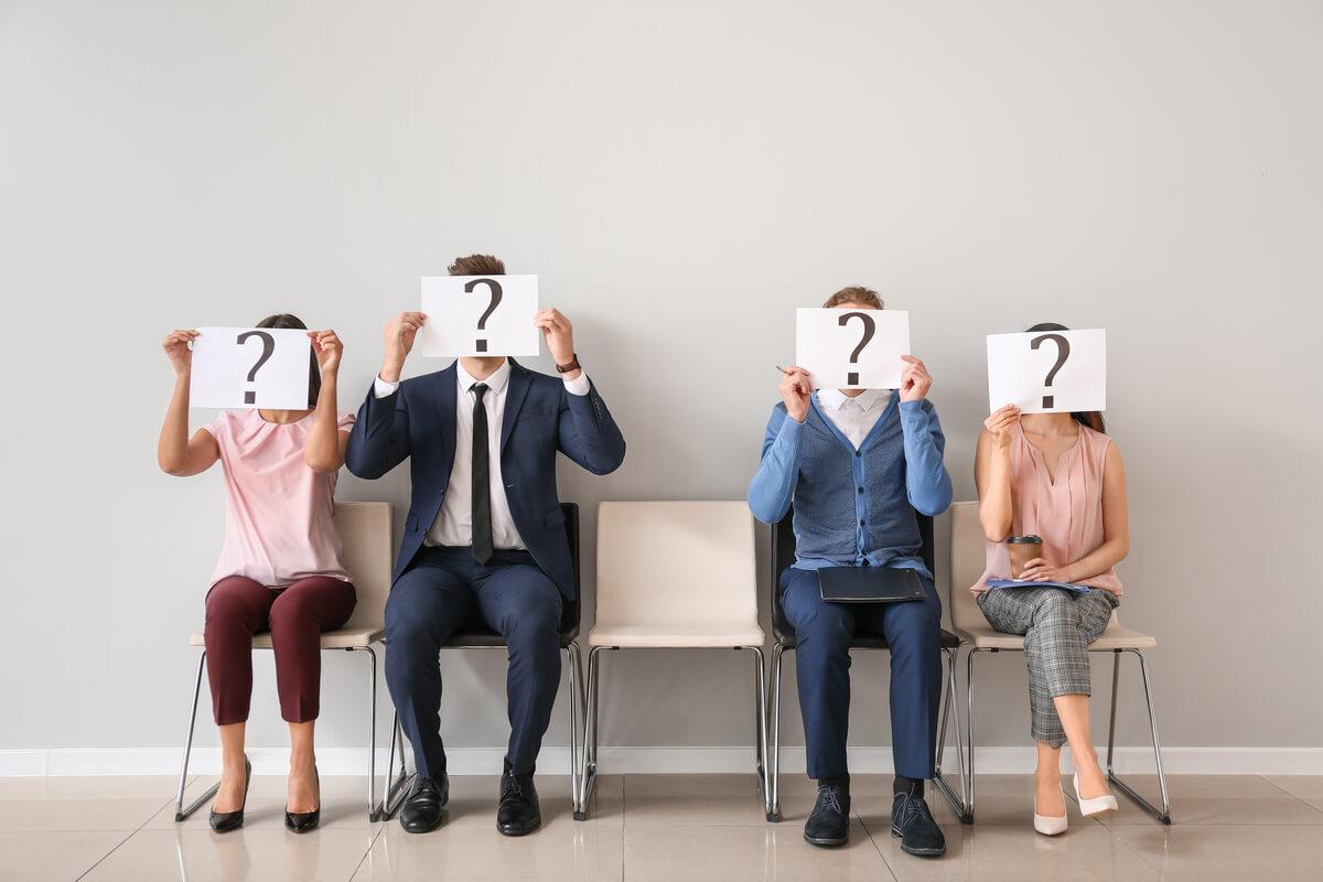Personas con un cartel con una interrogación sobre la cara