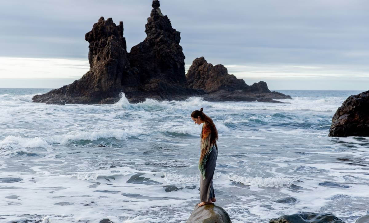Chica en una roca sobre el mar pensando en activar la inteligencia adaptativa