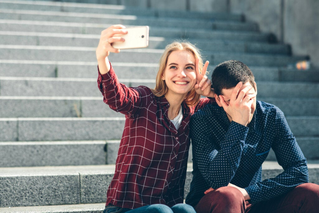 Chica haciéndose un selfie mientras su novio no quiere