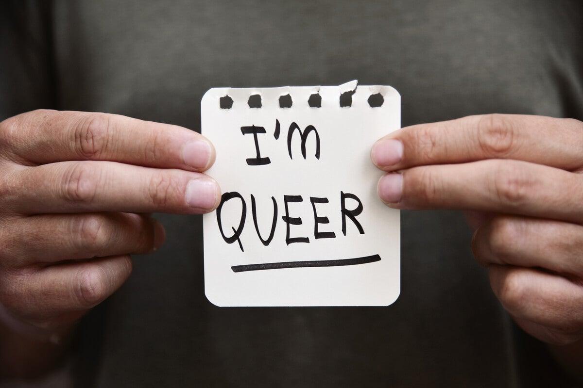 Persona con una nota en la que pone soy queer