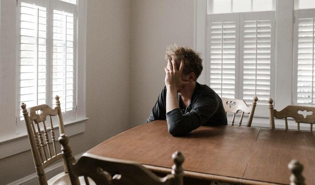 Chico agotado sobre una mesa debido a la fatiga por crisis