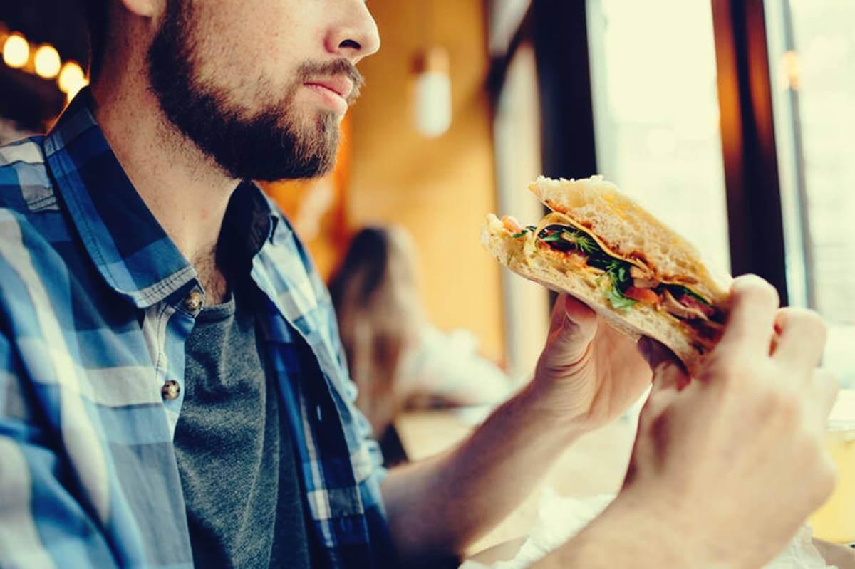 Hombre con bocadillo en las manos preguntándose por qué tengo hambre a todas horas