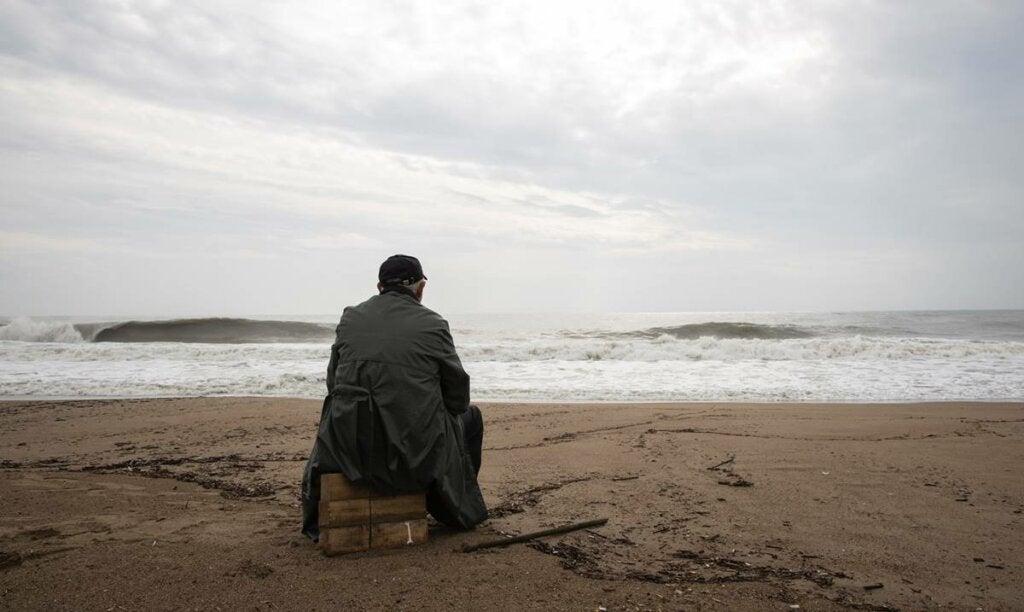 Hombre mirando el mar sobre madera pensando en el trastorno de estrés agudo