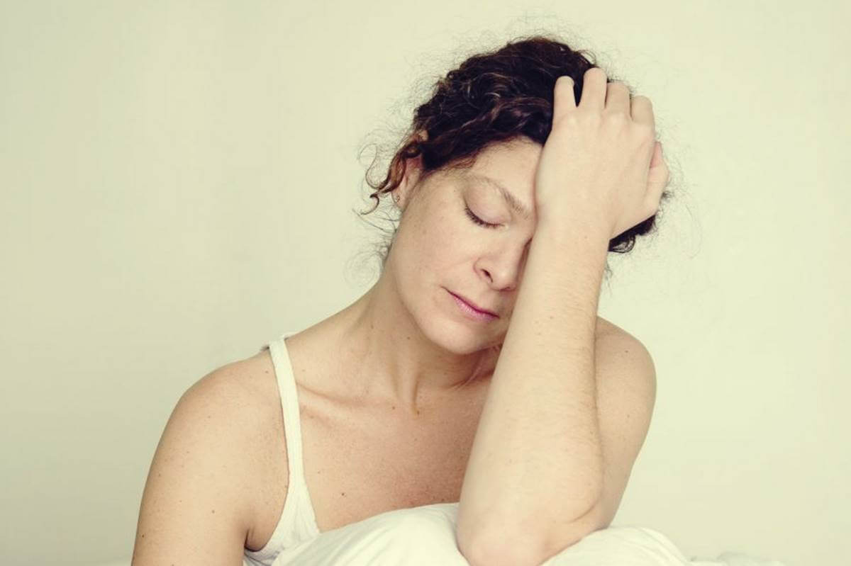 Mujer con mano en la cabeza preguntándose ¿Por qué estoy tan cansado cuando tengo ansiedad?