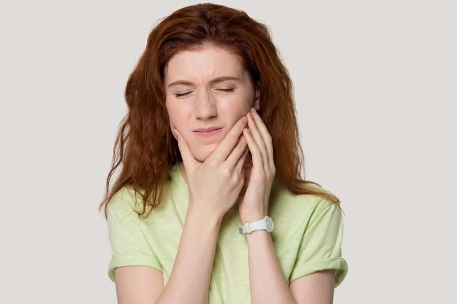 mujer que se coge la mandíbula porque sufre estrés y síndrome de tensión temporo-mandibular