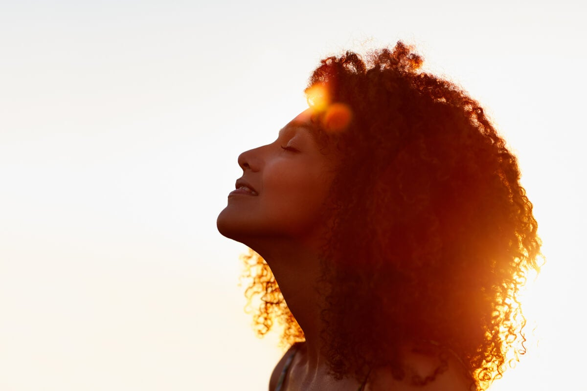 Mujer con los ojos cerrados meditando para reducir las manchas por estrés