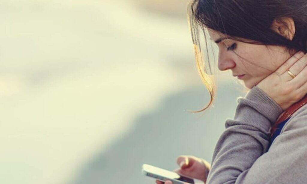 Mujer triste mirando el teléfono