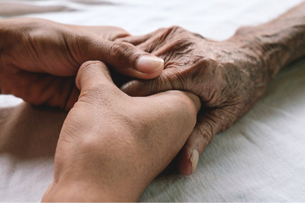 Persona agarrando la mano de su familiar