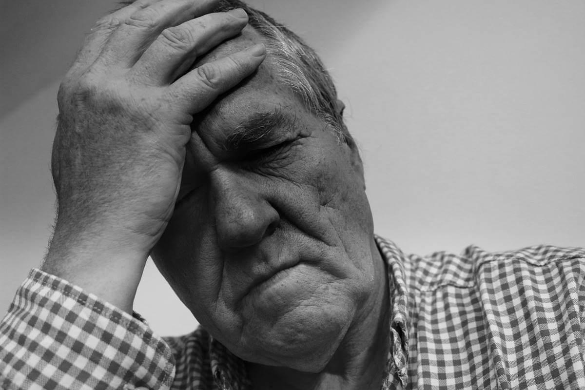 Hombre mayor que se lleva la mano a la frente debido a la bradipsiquia