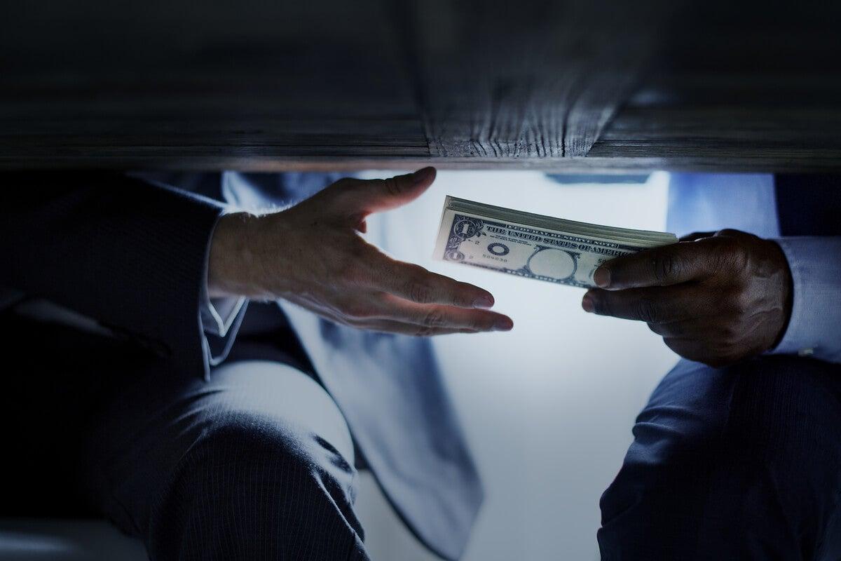 Personas pasándose dinero debajo de la mesa