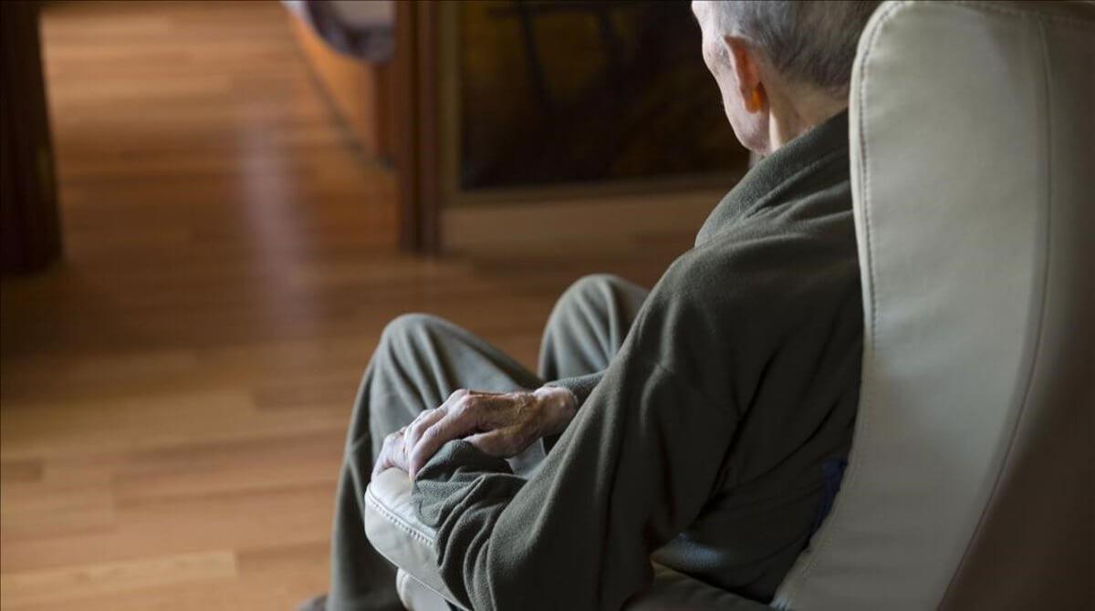 Hombre mayor en sofá representando la urgencia de saber cómo ayudar a un anciano maltratado