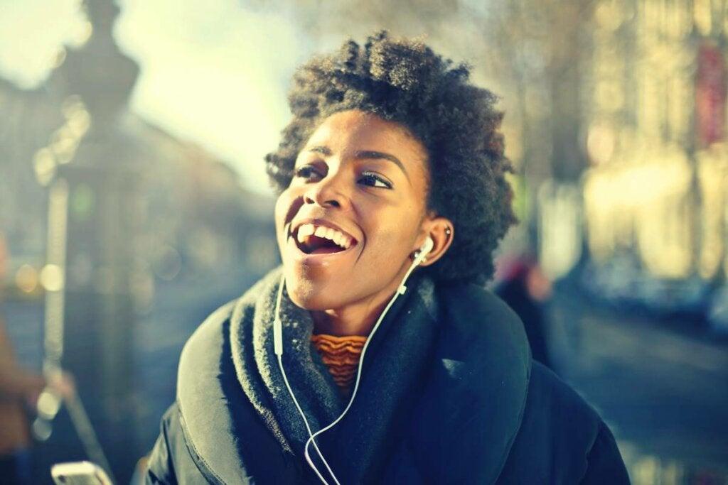 Chica feliz escuchando música en la fase de hipomanía