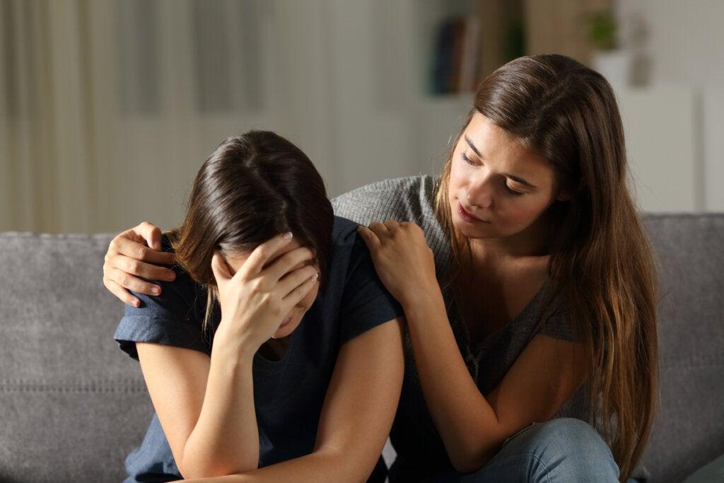 Chica triste por duelo con su amiga consolándola