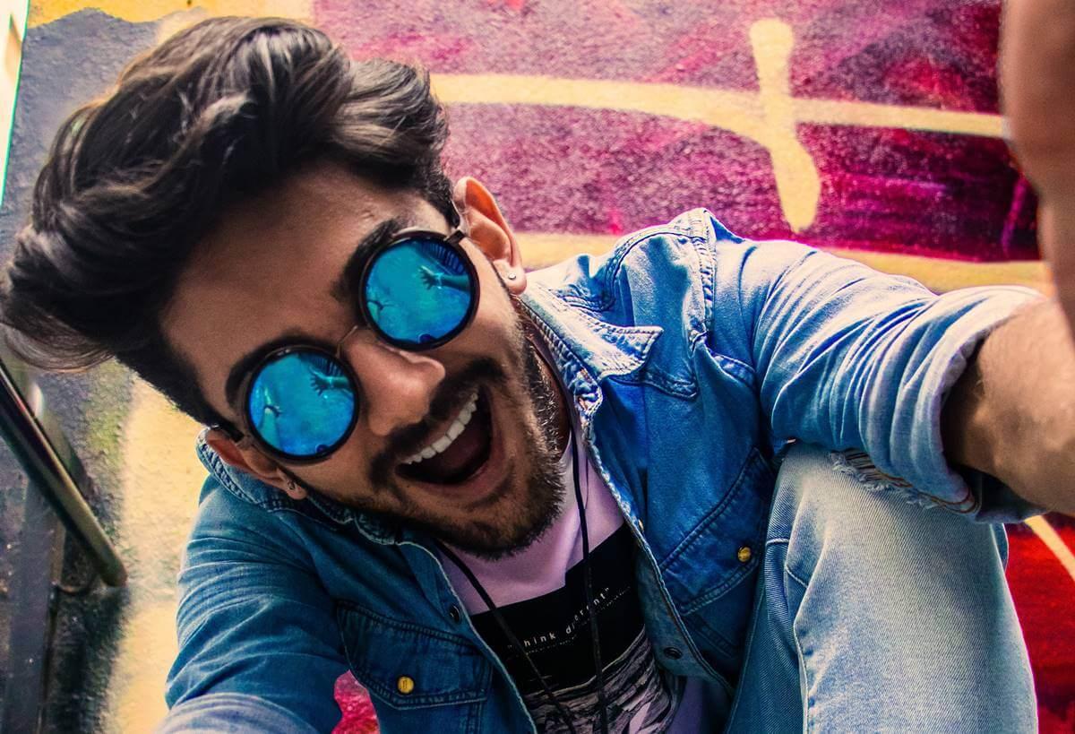 Chico eufórico con gafas azules en fase de hipomanía