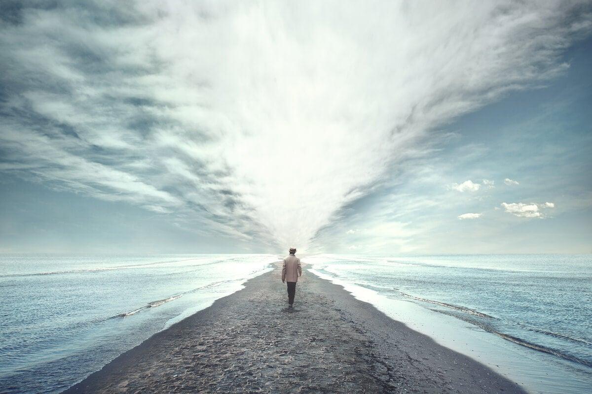 Hombre caminando hacia el mar en que tus problemas pueden ser un muro o una puerta