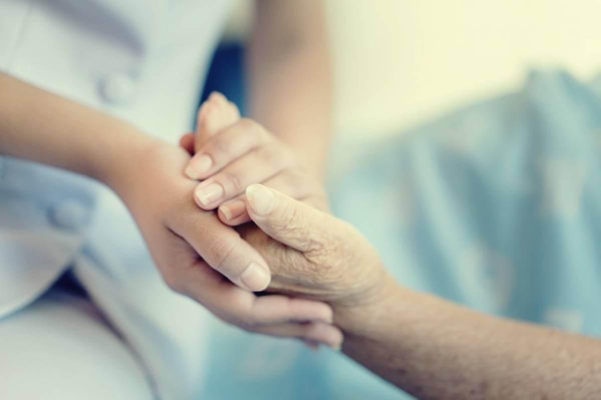 Persona cogiendo mano de anciano para representar la necesidad de ayudar a un anciano maltratado