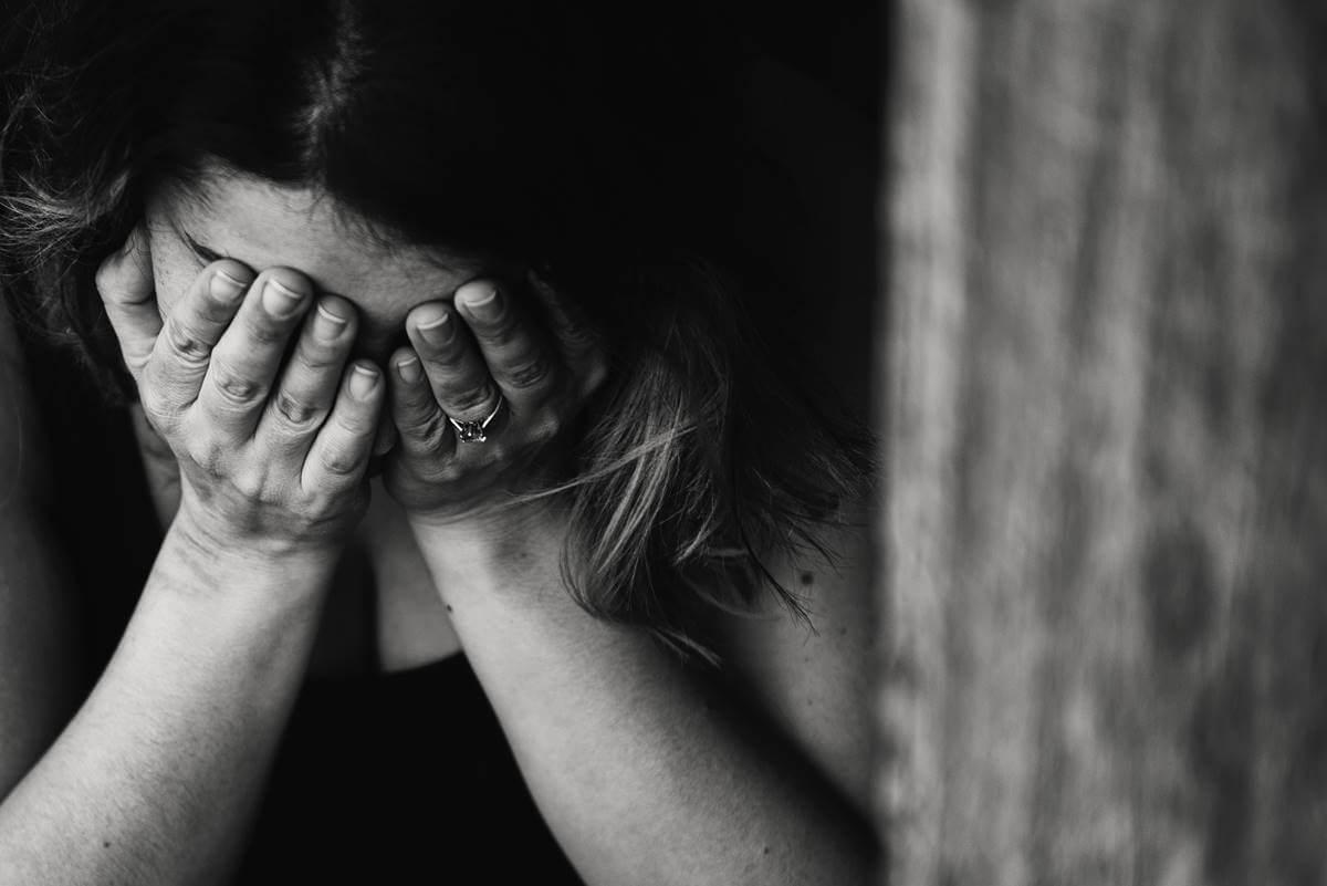 Mujer tapándose la cara para representar la relación entre vergüenza y depresión