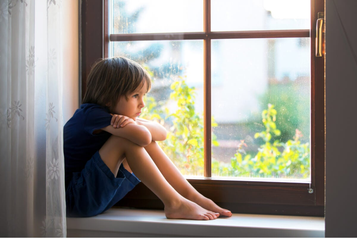 Niño mirando por la ventana representando las formas en que invalidan tus emociones