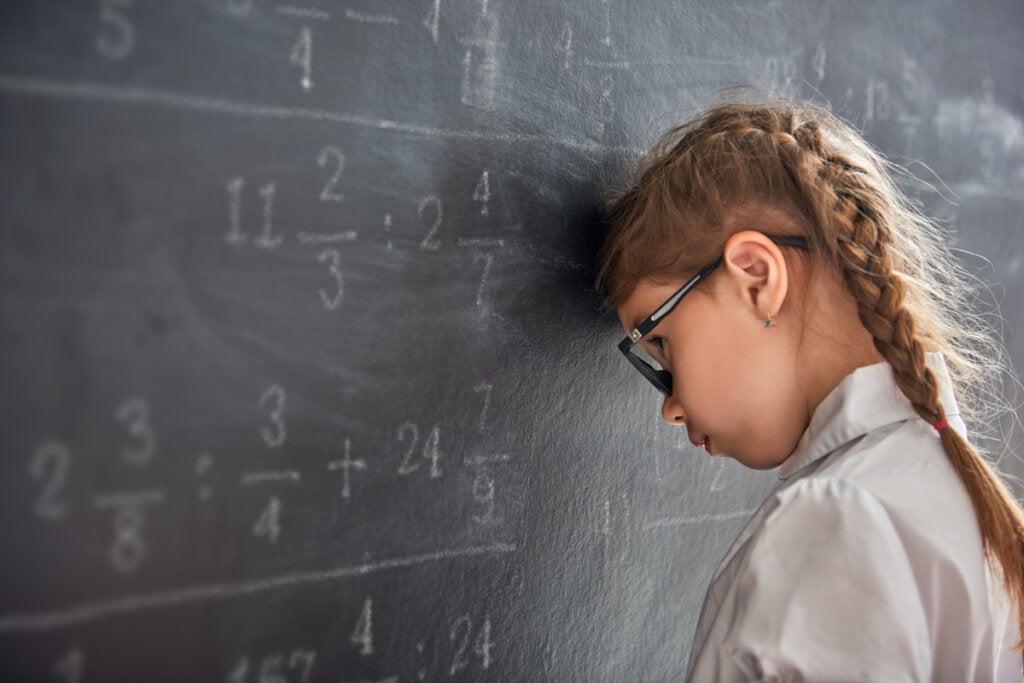 Alumna apoyando su cabeza en la pizarra