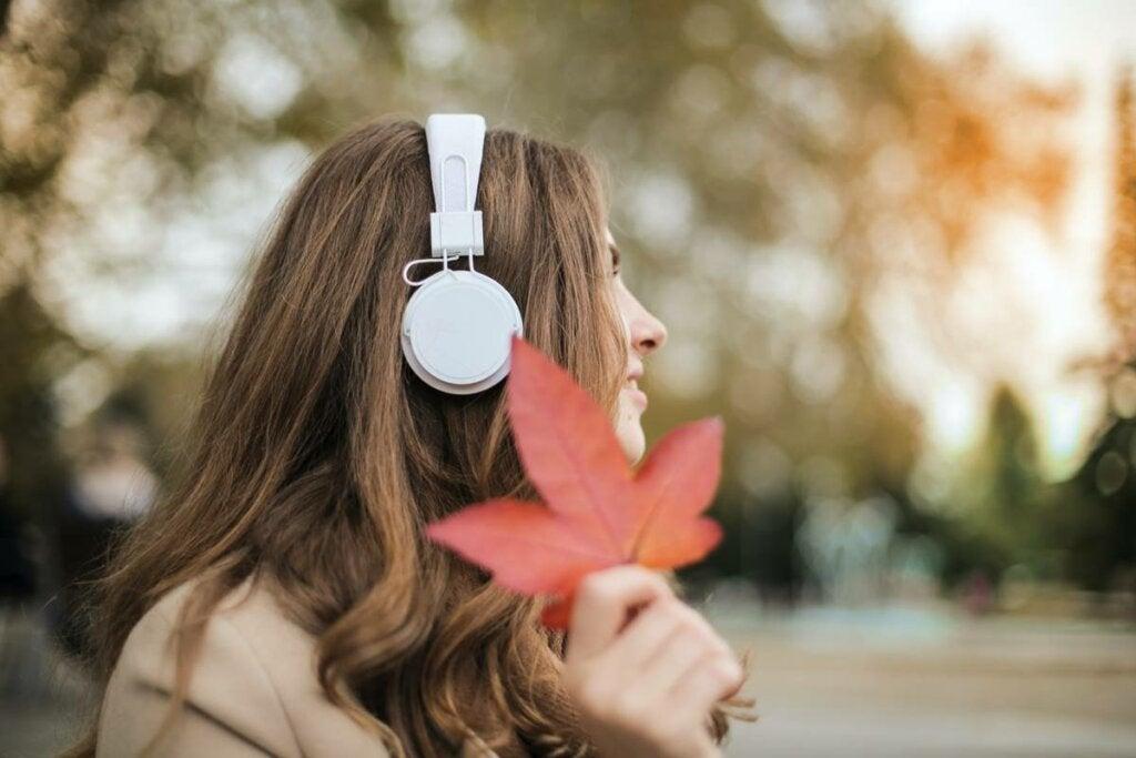 Chica con auriculares y hoja representando cómo afrontar la astenia otoñal
