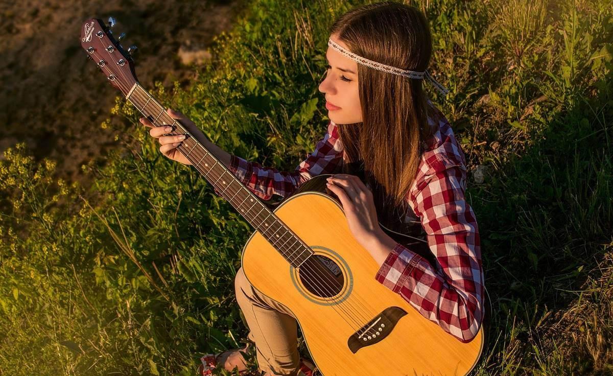 Chica tocando guitarra sintiendo las emociones musicales