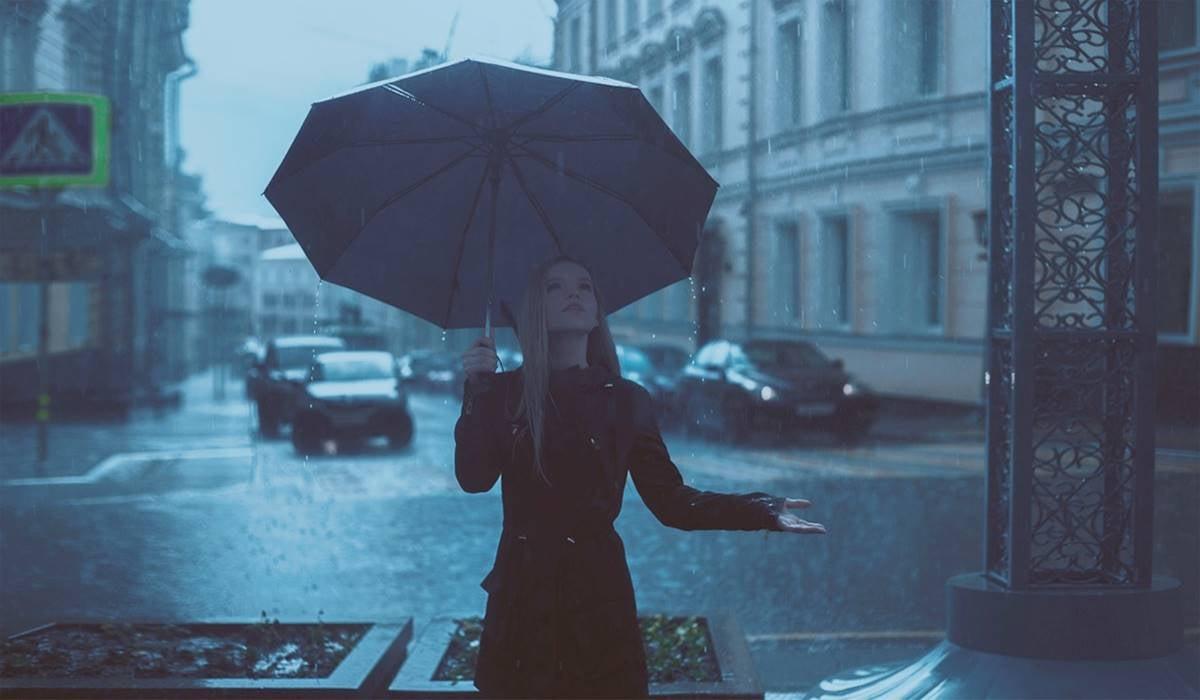 Chica con paraguas sufriendo la astenia primaveral