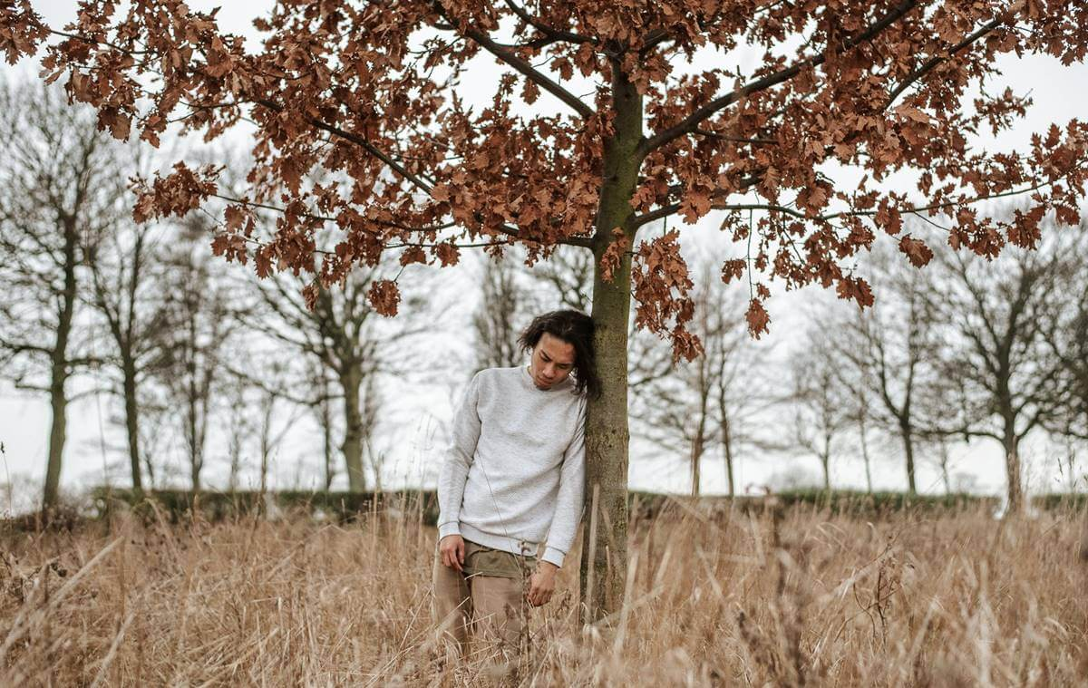 Chico apoyado en árbol pensando que me siento infravalorado por los demás