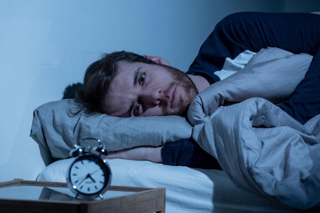 Hombre con insomnio pensando en cómo afecta el estrés al sueño