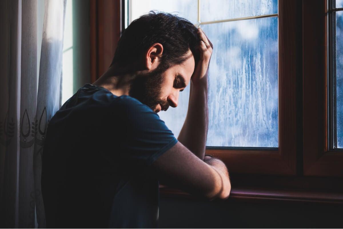 Hombre sintiendo culpa por la ventana