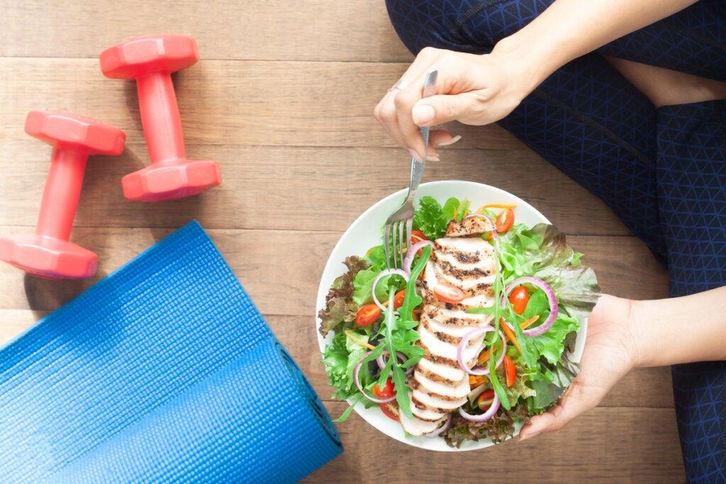 Mujer comiendo ensalada después de hacer ejercicio