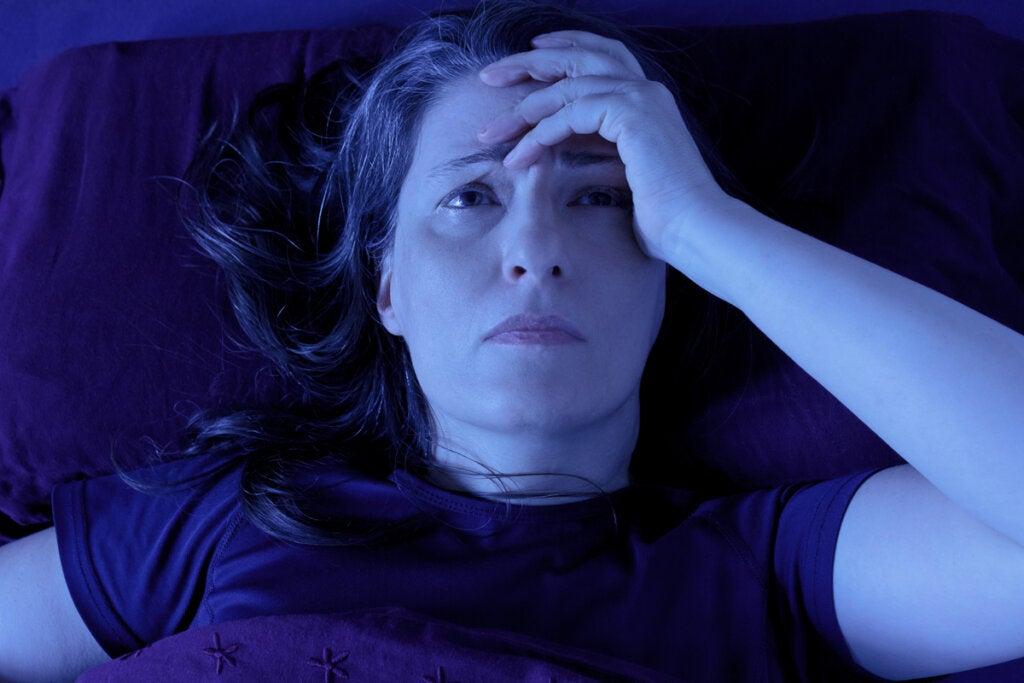 Mujer despierta en la cama sufriendo taquinesia