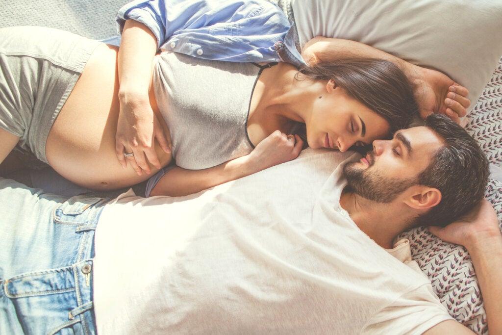 Mujer embarazada en la cama con su marido