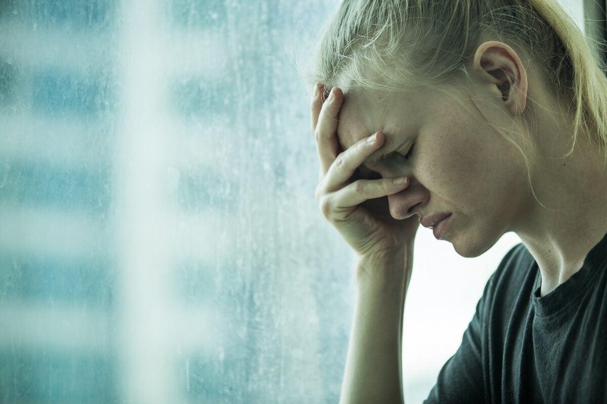 Mujer con la mano en la frente por ansiedad