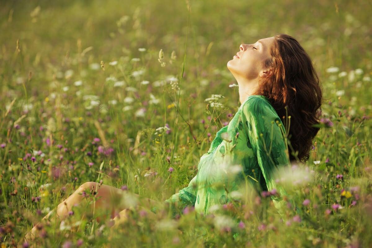 Mujer con ojos cerrados en el campo