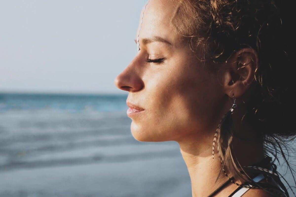 Mujer con los ojos cerrados practicando el escaneo corporal