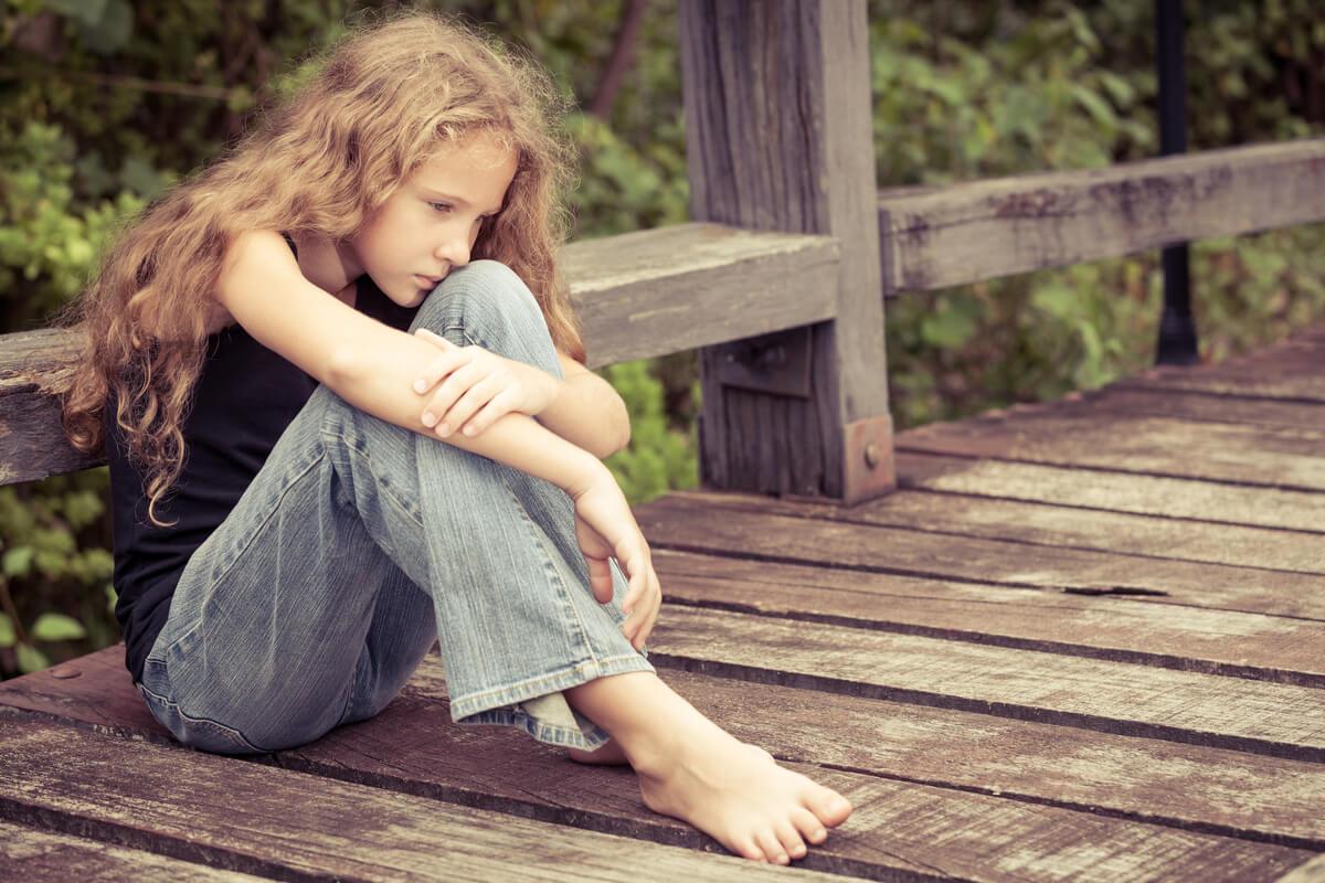 Niña con autismo sentada en el suelo