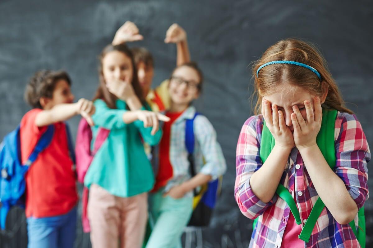 Niños riéndose de su compañera de clase