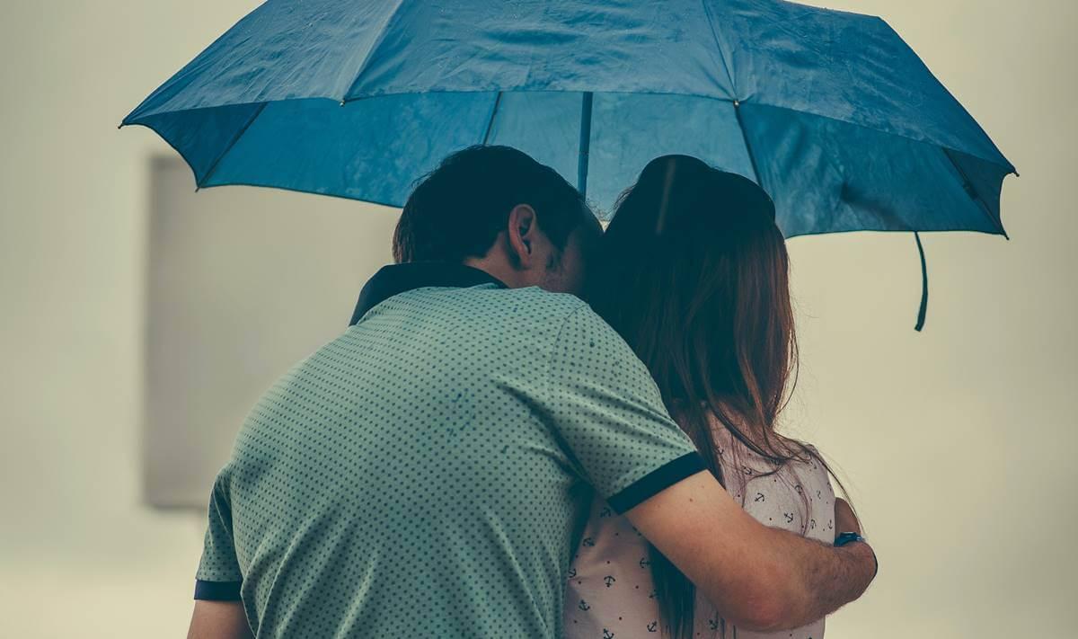 Pareja bajo el paraguas representando la diferencia entre amor infantil y amor maduro