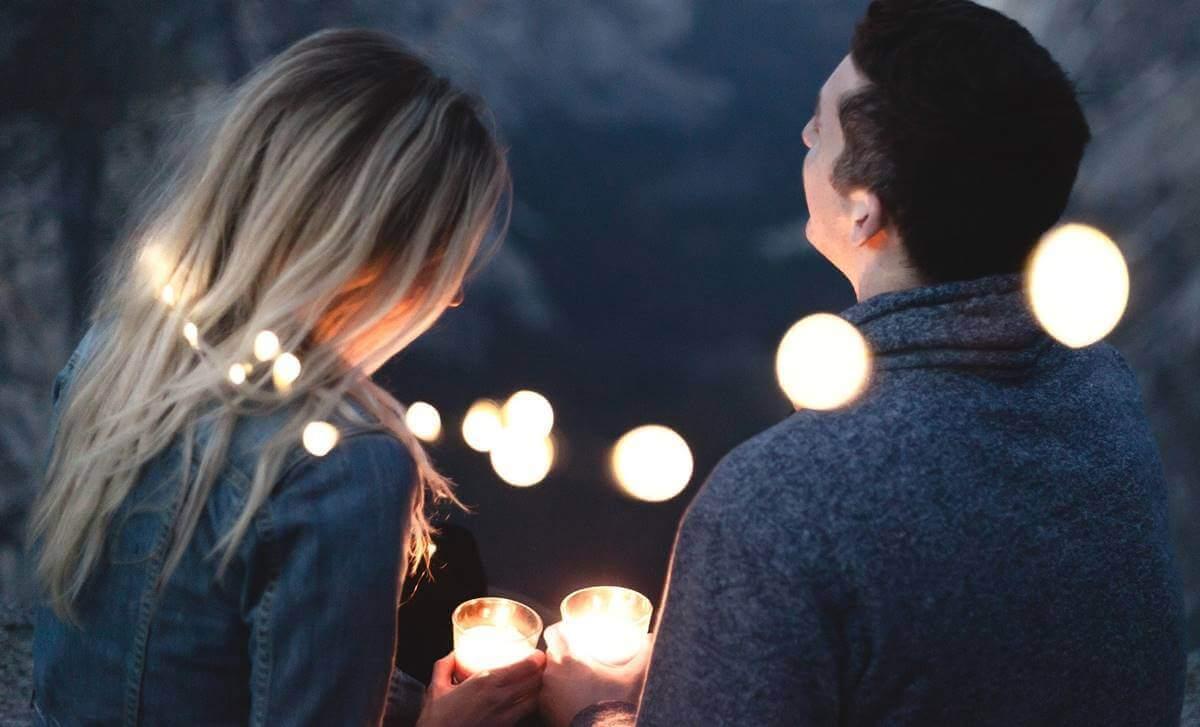 Pareja feliz rodeada de luces pensando en las preguntas para conocer mejor a tu pareja