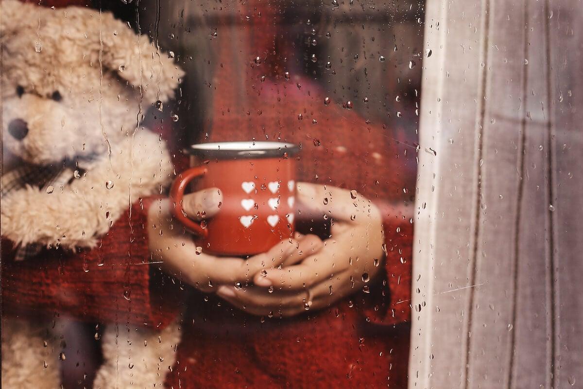 Persona viendo llover desde la ventana