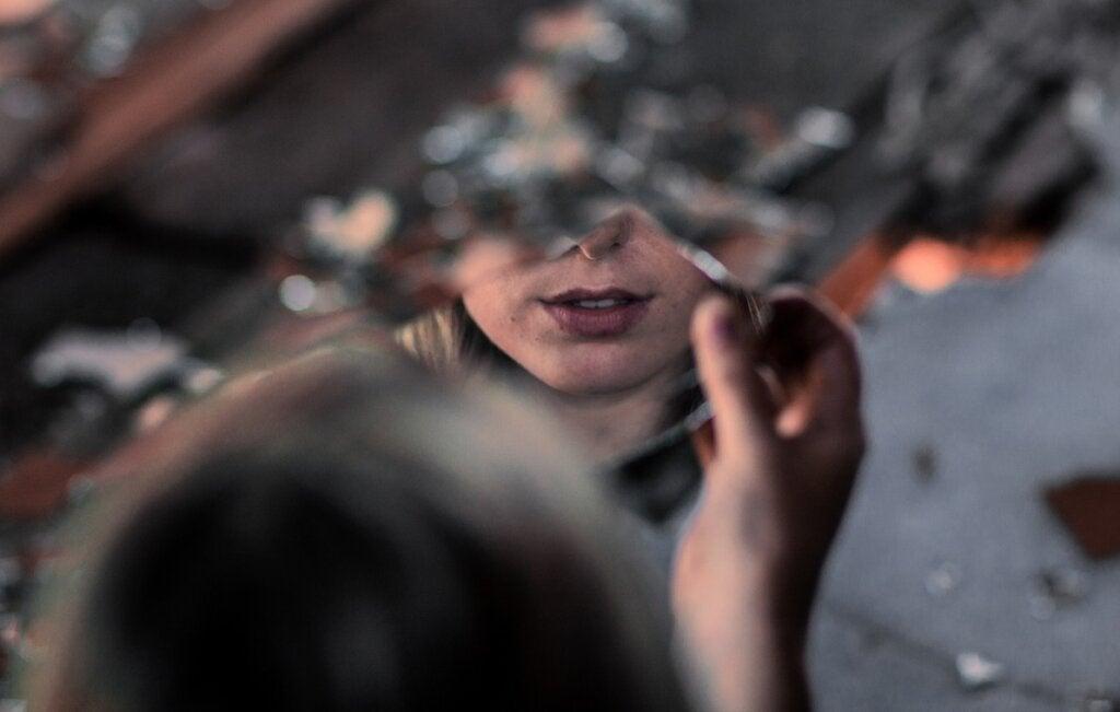 mujer ante espejo roto representando a las Hijas que no recibieron amor