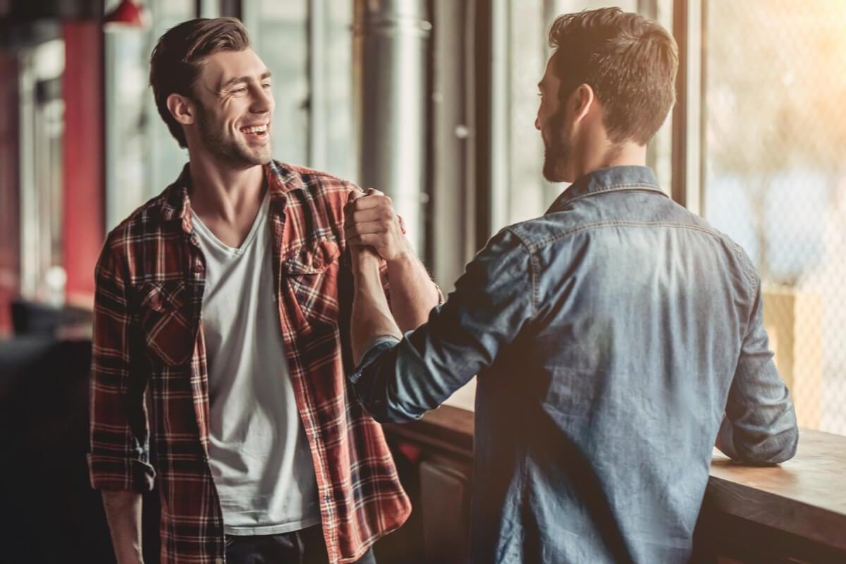 Dos amigos saludándose representando frases de amistad cortas y bonitas para dedicar