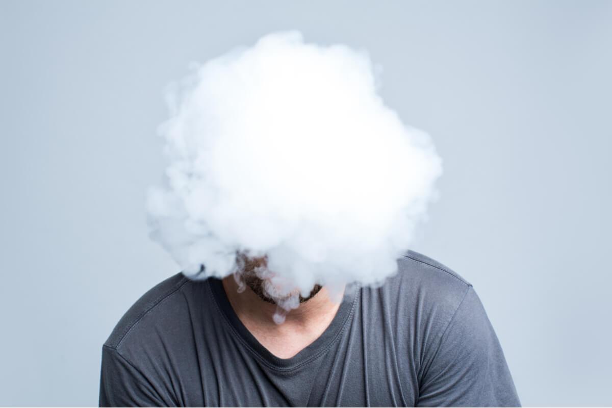 Hombre agotado con una nube en la cabeza preguntándose ¿Por qué es tan difícil controlar lo que pensamos?