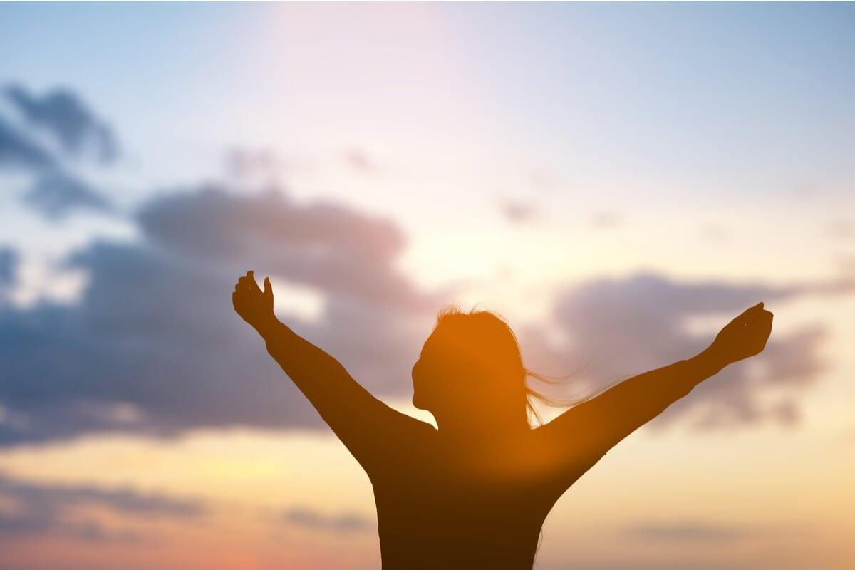 Mujer brazos abiertos observando el amanecer