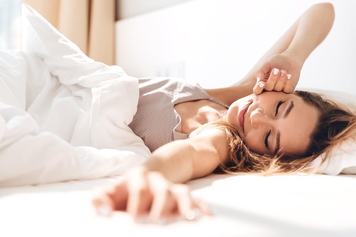 Mujer en la cama despertándose