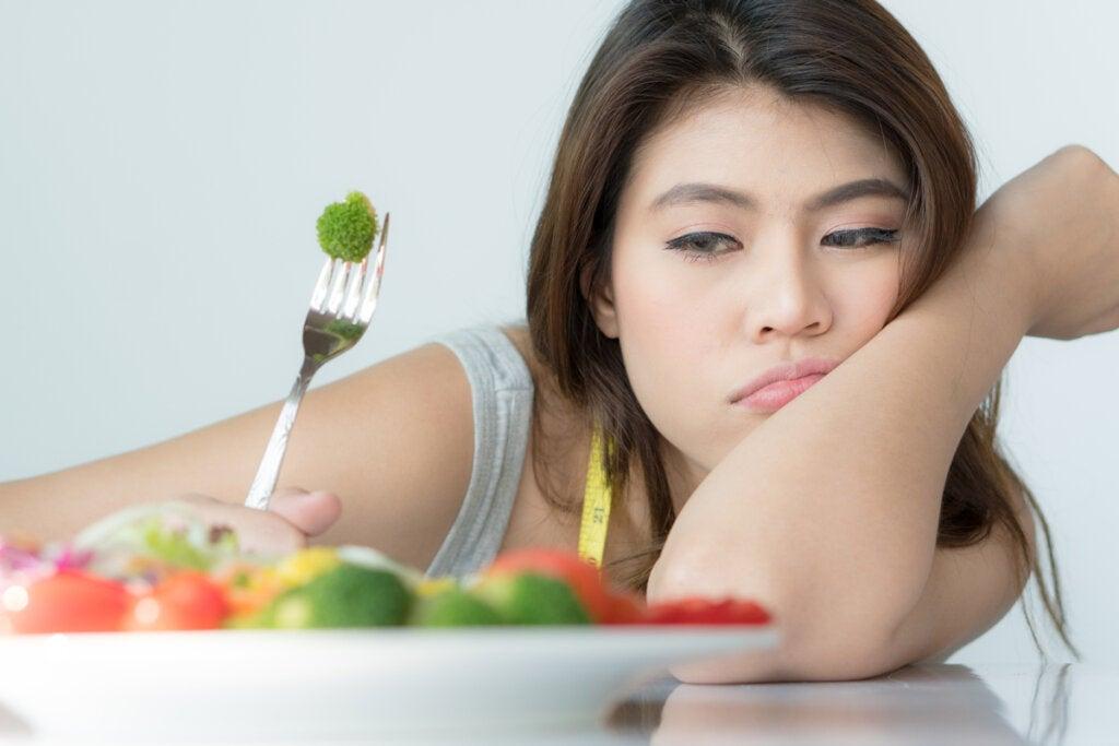 Mujer intentando comer vegetales