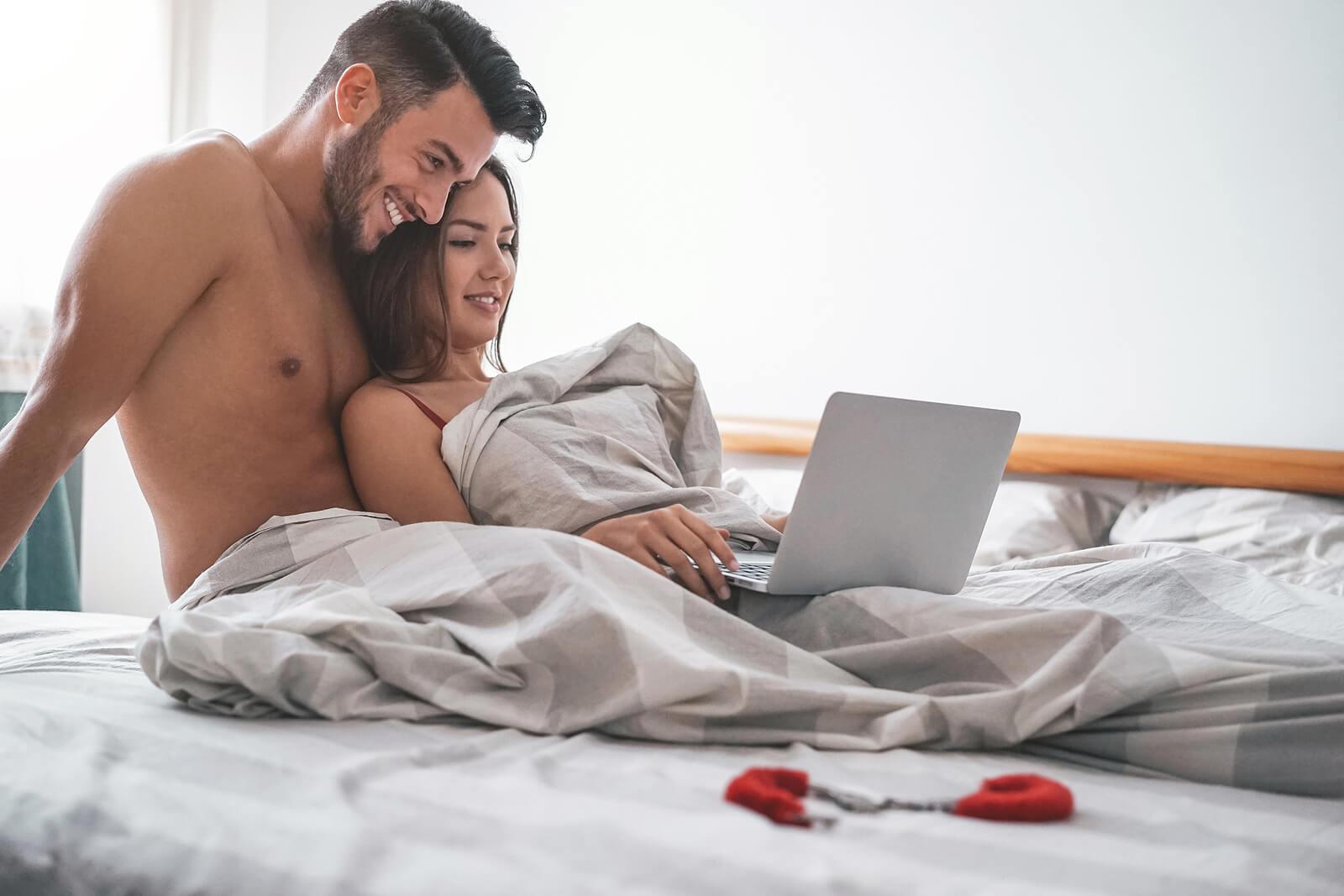 Pareja mirando el ordenador en la cama.