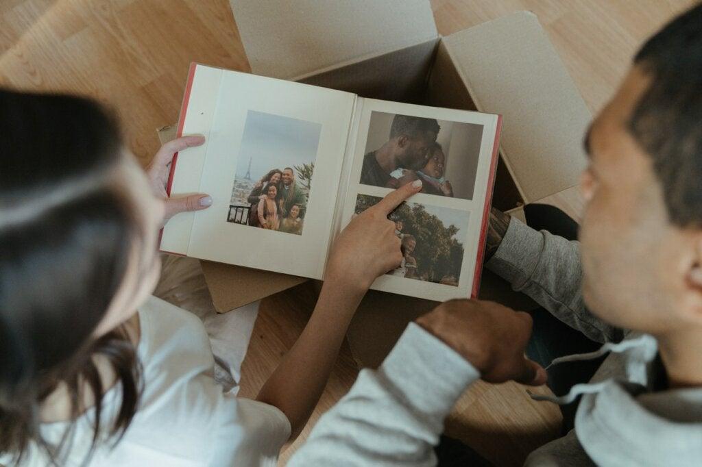 Pareja mirando un álbum de fotos, ejemplo de felicidad crepuscular.