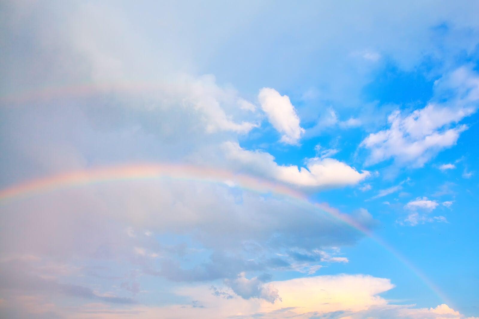 Arcoíris entre un cielo lluvioso y un cielo despejado.